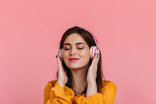 분홍색 벽에 헤드폰에 메이크업없이 만족 된 여자의 초상화. 즐거운 멜로디를 들으면서 웃는 모델.