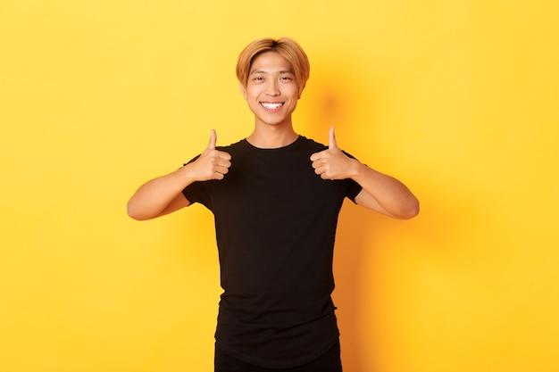 Портрет довольного красивого азиатского студента, показывающего в знак одобрения большие пальцы руки, стоящего на желтой стене