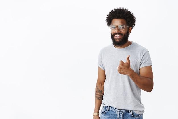 곱슬머리, 피어싱된 코, 엄지손가락 제스처를 보여주는 문신을 한 만족스럽고 카리스마 넘치는 아프리카계 미국인 남성의 초상화와 좋은 결과에 기뻐하는 미소