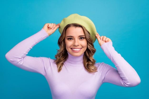 Портрет довольной прекрасной привлекательной девушки на синей стене