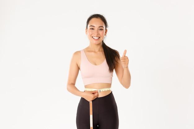 スポーツウェアで満足のいく笑顔、かわいいアジアの女の子の肖像画、巻尺でウエストを測定した後、親指を立てて、体重を減らしました。
