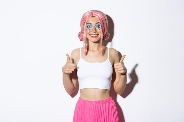 Портрет довольной улыбающейся девушки, показывающей большие пальцы в одобрении, хвалят хороший выбор
