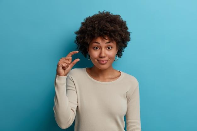 자연스러운 곱슬 머리를 가진 만족스러운 여성의 초상화는 손을 들고 작은 것을 만들고 무언가의 작은 크기를 말하며 성공을 얻는 데 약간의 노력이 든다고 말하며 캐주얼 한 흰색 스웨터를 입습니다.