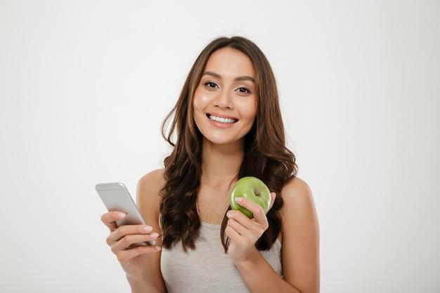 Портрет довольной женщины с идеальной улыбкой, используя серебряный смартфон и есть свежее зеленое яблоко, изолированное над белой стеной