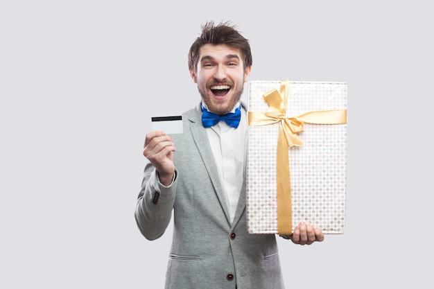 Портрет довольного молодого взрослого человека в сером пальто и синем галстуке-бабочке, стоящего и держащего подарок с желтым бантом и банковской кредитной картой, глядя на камеру. крытый, изолированный, студийный снимок, серый фон