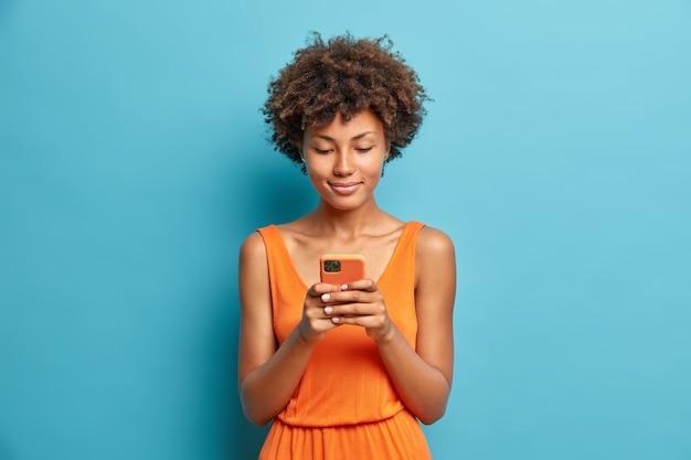 満足している若い女性の肖像画は、スマートフォンでニュースフィードをチェックし、裸の肩でドレスポーズを着ています。青い壁に隔離された高速インターネットを使用しています。