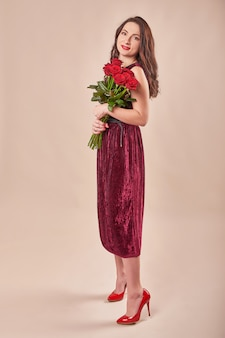 バラの花束と赤いドレスで満足している若い女性の肖像画