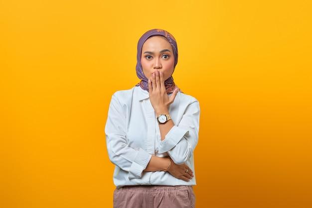 Портрет испуганной азиатской женщины, слушающей плохие новости на желтом фоне