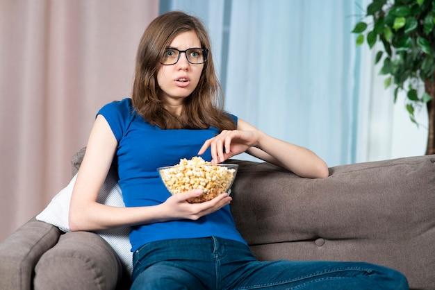 Портрет испуганной заинтересованной девушки в очках молодая женщина смотрит интересный ужастик