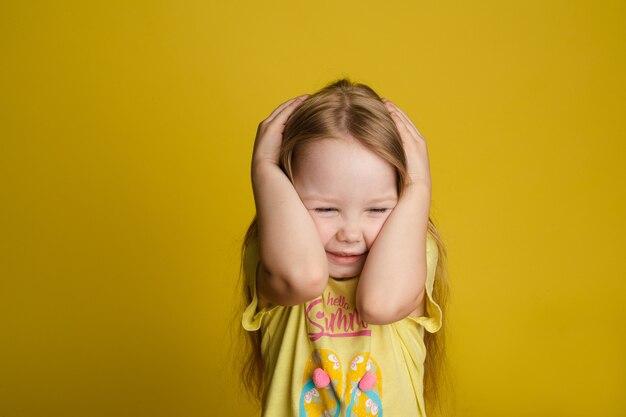 黄色のスタジオの背景で分離されたポーズの手で頭を閉じる怖い少女の肖像画