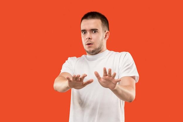 怖い男の肖像画。トレンディなオレンジ色に孤立して立っている男