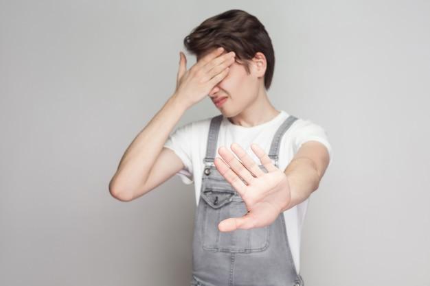 デニムのオーバーオールが手を閉じて目を閉じて立って、ブロックし、禁止ジェスチャーを示しているカジュアルなスタイルの怖いまたは恥ずかしがり屋の若いブルネットの男の肖像画。灰色の背景に分離された屋内スタジオショット。