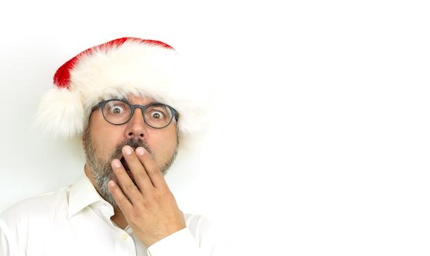 白い背景にクリスマスの帽子をかぶって怖がってまたは驚いた男の肖像画。