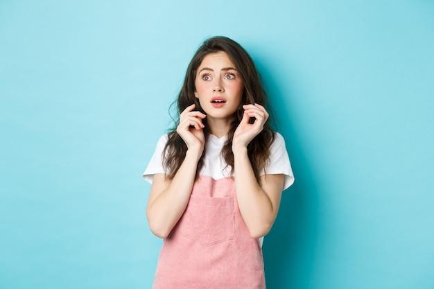夏服を着た怖い臆病な少女の肖像画、コピースペースのバナーを怖がって見て、怖いものからジャンプし、青い背景に立っています。