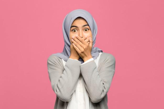 怖い若いアジアの女性の肖像画は手のひらで口を覆った