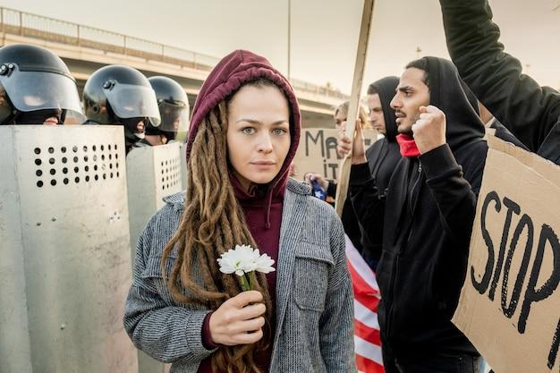Портрет испуганной молодой кавказской женщины со страхами, стоящей с ромашками между полицией и протестующими на митинге
