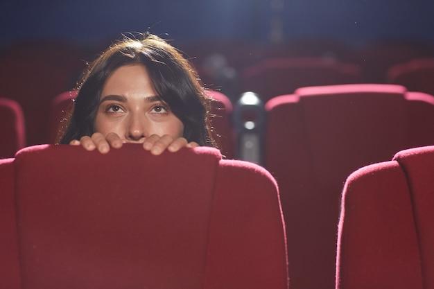 Портрет испуганной молодой женщины, прячущейся за сиденьем во время просмотра фильма ужасов в пустом кинозале, копией пространства
