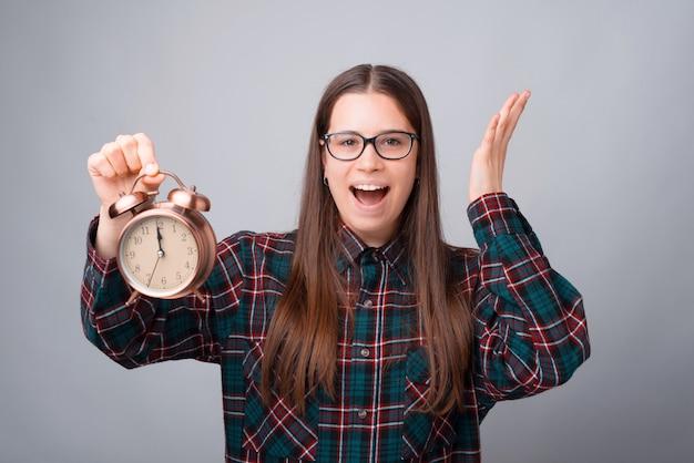 灰色のbackgorundで目覚まし時計を保持している怖がっている若い女性の肖像画