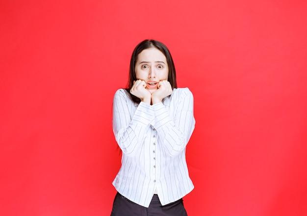 赤い背景の上のカメラを見ている怖い若い女性の肖像画。