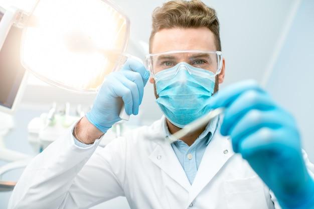 カメラを見て手術中に歯科用ツールでマスクと保護眼鏡で怖い歯科医の肖像画