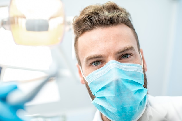 カメラを見て手術中に歯科用ツールとマスクで怖い歯科医の肖像画