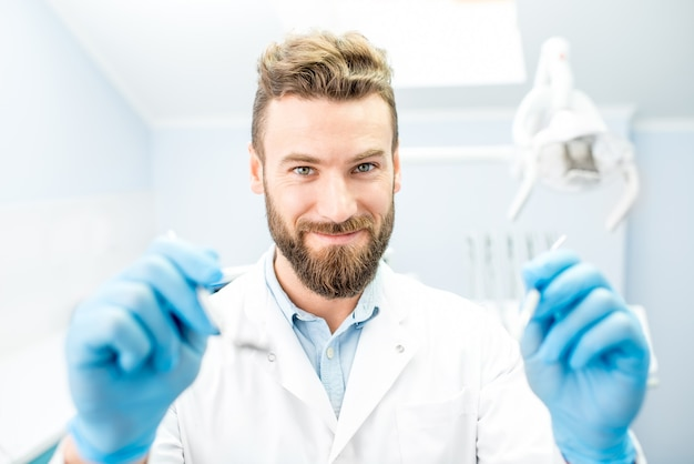 Портрет страшного стоматолога со стоматологическими инструментами, глядя в рот на камеру