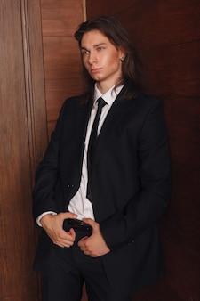 학교 소년의 초상화입니다. 검은 양복, 넥타이, 흰색 셔츠, 주머니에 손, 캠퍼스의 빈티지 스타일 사무실 문에 서서 당신을 바라보는 젊고 잘 생긴 대학생.