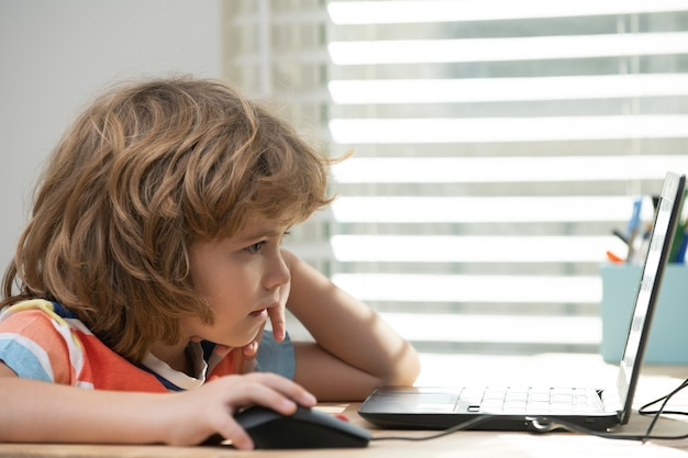 Портрет школьника, глядя на ноутбук во время урока. первый день в школе. милый маленький ребенок учится.