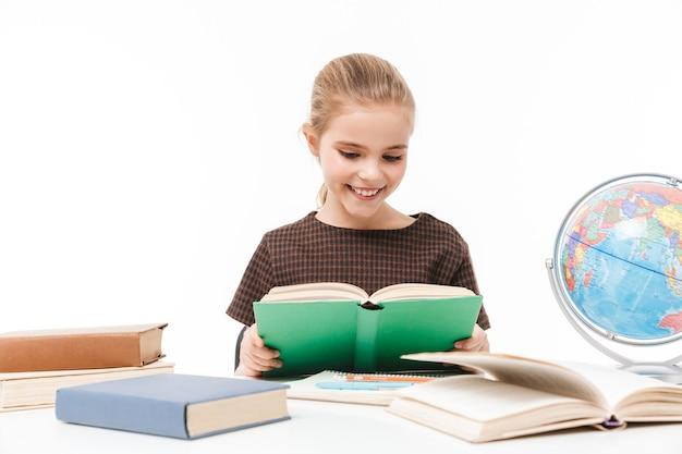 白い壁に隔離されたクラスの机に座って本を読んで宿題をしている女子高生の肖像画
