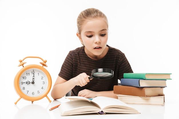 白い壁に隔離されたクラスで勉強し、本を読んで机の上に大きな目覚まし時計を持つ女子高生の肖像画