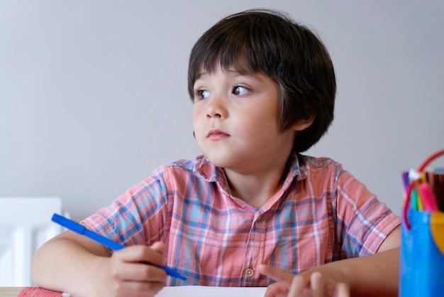 テーブルの上に立地し、思考の顔で外を見て学校の子供男の子の肖像画