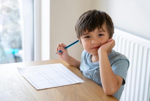 Портрет школьника, сидящего на столе, делая домашнее задание