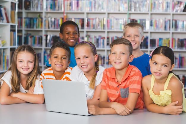 ライブラリでノートパソコンを使用している学校の子供たちの肖像画