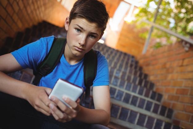 階段で携帯電話を使用している少年のポートレート