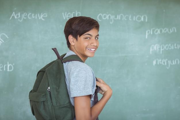 Портрет школьника с рюкзаком, стоящим на доске в классе