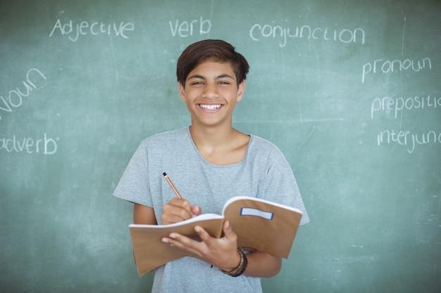 Портрет школьника, пишущего в записной книжке на доске в классе