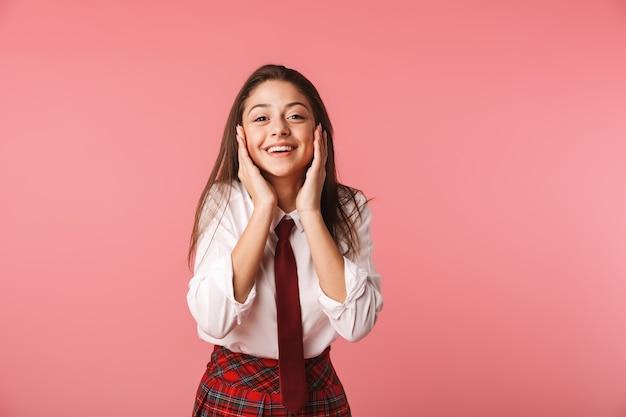 赤い壁に隔離された制服立っている女子高生15-16yの肖像画