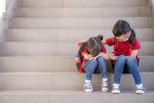 彼女を慰める笑顔の妹と屋外の階段に座って泣いている女子高生の肖像画、コピースペース