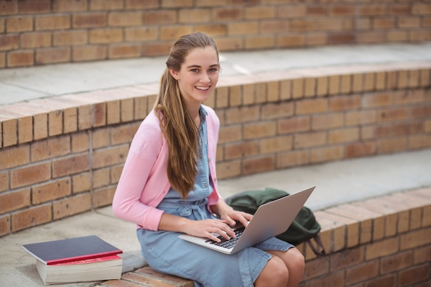 キャンパスでラップトップを使用して女子高生の肖像画