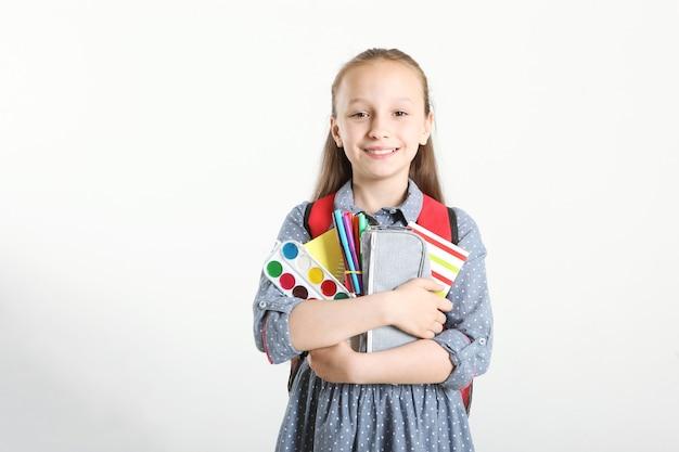 Портрет школьницы с рюкзаком и канцелярскими принадлежностями