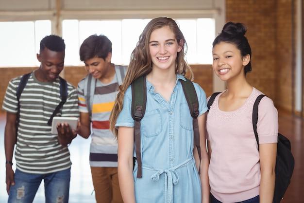 バックグラウンドでクラスメートとクラスメートと立っている女子学生の肖像画