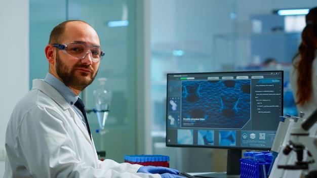 近代的な設備の整った実験室に座っているカメラを見ている科学者の男の肖像画。科学研究のためのコンピューター化学ツールでハイテクタイピングを使用してウイルスの進化を調べる科学者の医師