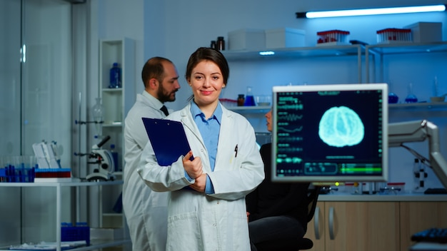 Портрет ученого-невролога-исследователя, смотрящего в камеру, улыбается, пока коллега обсуждает с пациентом на заднем плане функции мозга, нервную систему, томографическое сканирование, работающее в лаборатории