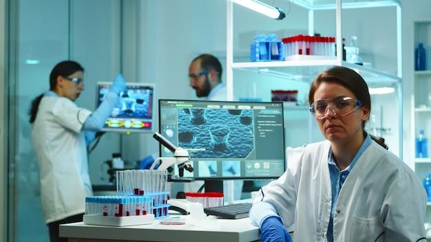 늦은 밤에 현대적인 시설을 갖춘 실험실에 앉아 카메라를 보고 피곤해 보이는 과학자 간호사의 초상화. 연구, 백신 개발을 위해 첨단 기술을 사용하여 바이러스 진화를 조사하는 전문가 팀