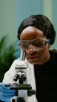 의료 실험을 위해 현미경으로 슬라이드를 얹은 마이크로피펫으로 잎 샘플을 채취하는 과학자의 초상화. 미생물학 과학 실험실에서 유기 농업 식물을 분석하는 화학자