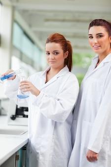 Erlenmeyer flasの青い液体を注ぐ科学者の肖像