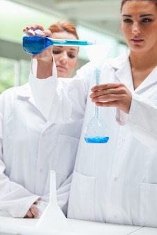 Portrait of scientists pouring liquid into a flask