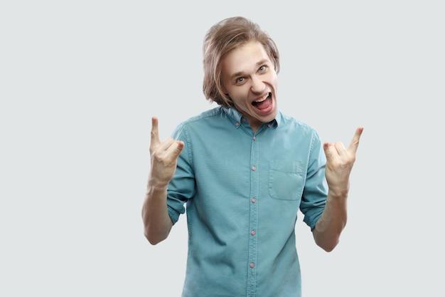 ロックサインと立って、カメラの叫びを見て青いカジュアルシャツでハンサムな長い髪の金髪の若い男の叫び声の肖像画。明るい灰色の背景に分離された屋内スタジオショット。