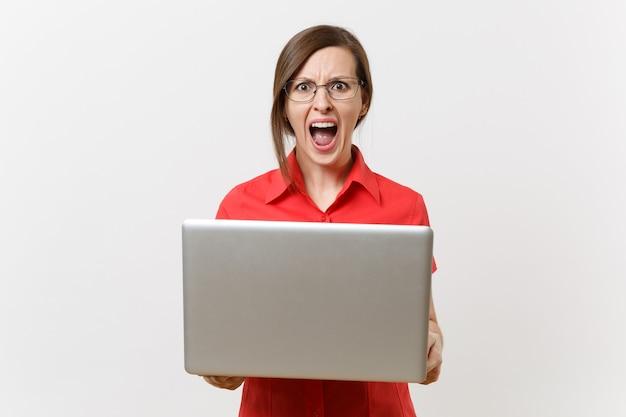 赤いシャツ、白い背景で隔離のラップトップpcコンピューターでタイピング作業メガネで叫んでいる若いビジネス教師の女性ユーザーの肖像画。高校大学の概念における教育または教育