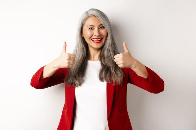 Портрет пожилой азиатской женщины, показывающей большой палец вверх в одобрении, в красном пиджаке для офисной работы, рекомендую компанию, стоящую на белом фоне
